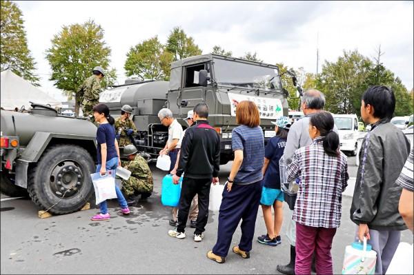 日本自衛隊提供災區乾淨的飲用水,北海道居民默默排隊領取。(法新社)