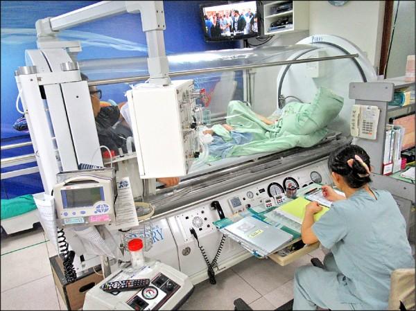 ▲患者躺在艙裡接受高壓氧治療,期使缺氧的腦組織快速且充分地獲得氧氣供應。(照片提供/黃敦郁)