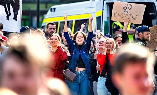 瑞典民眾八日在極右派的瑞典民主黨造勢活動場外,高舉中指抗議。(歐新社)