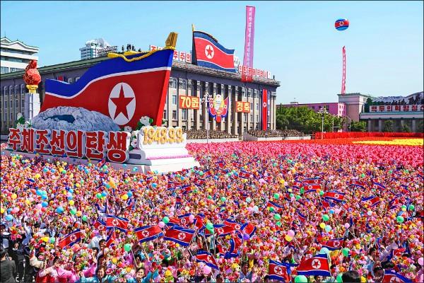 參與閱兵的北韓民眾手持國旗、花朵和氣球,向金正恩揮手歡呼。(法新社)