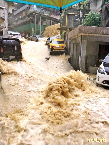 基隆市昨早瞬間暴雨,造成新西街207巷積水處處,泥水從擋土牆直衝而下,宛若瀑布,居民自嘲我家門前就有「十分瀑布」。(記者俞肇福攝)