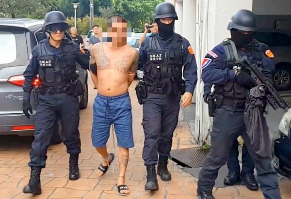 涉及南投縣竹山鎮「行刑式」槍殺案的許姓嫌犯,今日遭警方逮捕,連上衣也來不及穿就被押解到竹山分局偵辦。(記者謝介裕翻攝)