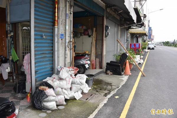 屏東市光復路局民家家戶戶準備沙石對抗淹水。(記者葉永騫攝)