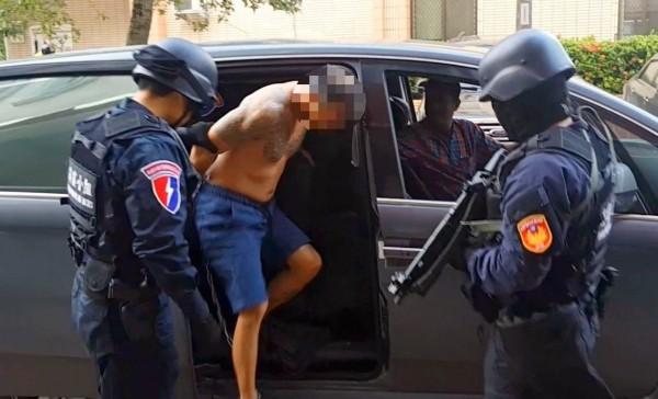 南投警方全副武裝押解涉及「行刑式」槍殺茶農的嫌犯許育洲下車。(記者謝介裕翻攝)