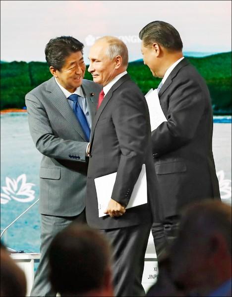 俄羅斯總統普廷(中)、日本首相安倍晉三(左)和中國國家主席習近平(右),十二日出席俄羅斯海參崴舉行的東方經濟論壇。(美聯社)