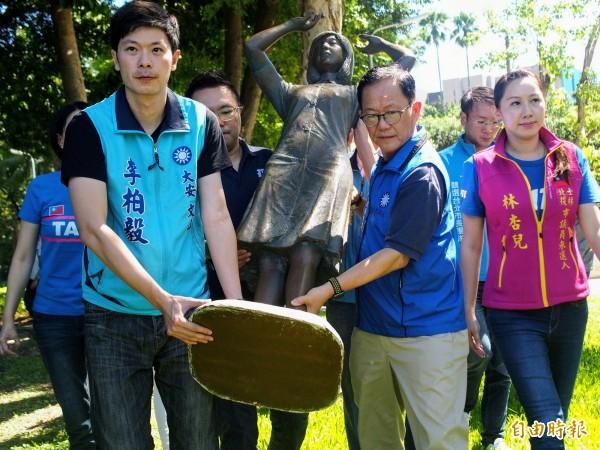 國民黨台北市長參選人丁守中(右二)今天上午扛起復刻版慰安婦銅像進到二二八公園召開記者會。(記者簡惠茹攝)