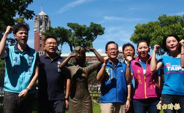 國民黨台北市長參選人丁守中(右四)今天上午扛起復刻版慰安婦銅像進到二二八公園召開記者會。(記者簡惠茹攝)