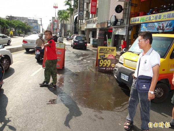機車行師傅在場協助指揮人車慢行通過油漬區路面。(記者王俊忠攝)