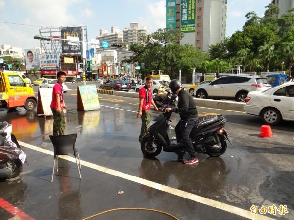 機車行師傅協助摔倒的機車騎士起身整理人車。(記者王俊忠攝)