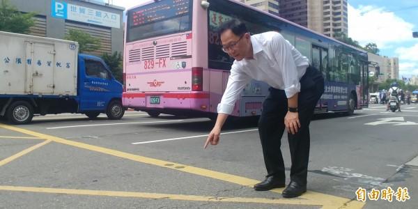 國民黨台北市長參選人丁守中今天把記者會拉到馬路上開,指著坑坑疤疤的路面,批評台北市長柯文哲不把路平當回事。(記者簡惠茹攝)