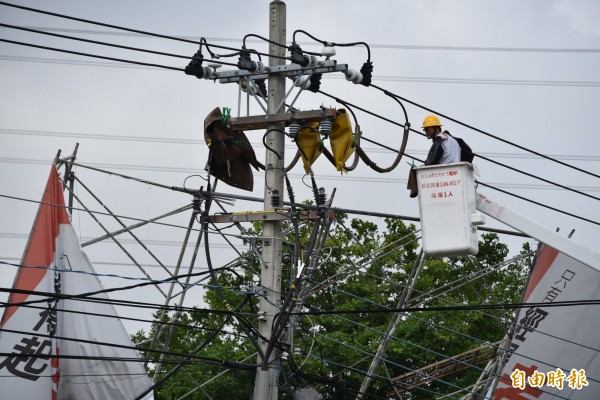 台電人員正辛苦的忙著搶修電力。(記者葉永騫攝)