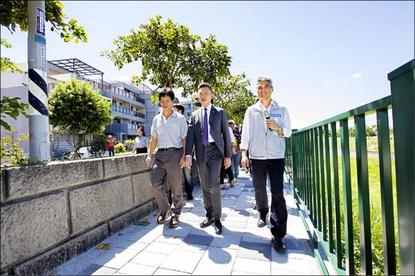 新竹市府投入兩千萬元經費在客雅溪堤岸頂雅橋至牛埔橋路段鋪設步道昨天啟用,市長林智堅(中)帶頭步行。(市府提供)