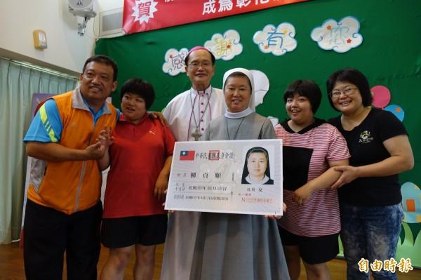 鹿港聖母聖心啟智中心修女柳貞順(圖右三),拿到台灣身分證,慢飛天使與家人開心與修女合照。(記者劉曉欣攝)