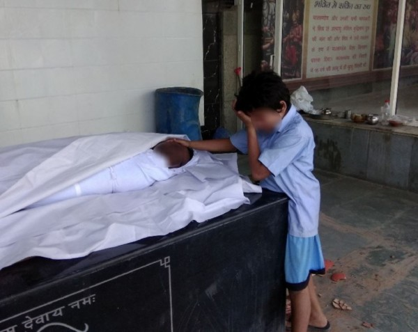 印度1名記者前天拍下了1張男童在父親遺體前掩面啜泣的照片,該名記者將照片PO上網後,引起廣大迴響。(圖擷取自推特)