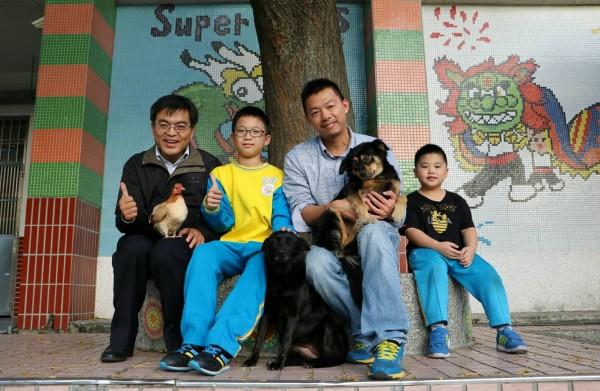 鍾孝昇(右二)成立「動物保護社」收養流浪動物,讓學生們透過餵養等過程學習尊重生命。(鍾孝昇提供)