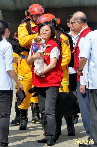 蔡英文總統昨日出席國家災防日演練,抱起搜救犬「樂樂」與搜救隊員在空軍運輸機前合影留念。(記者張嘉明攝)