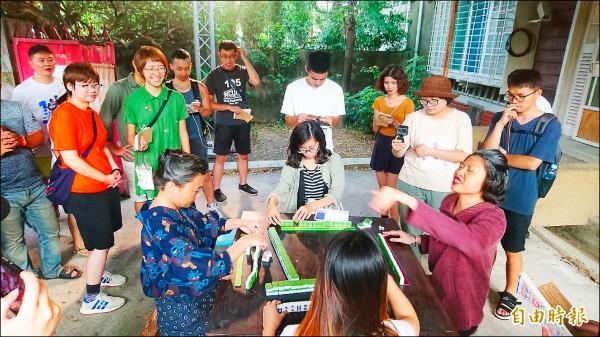 突然現身的戲劇演員,拉著現場遊客一起打麻將,讓遊客也成為戲中一角。(記者劉婉君攝)