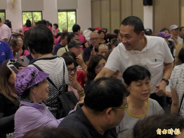 國民黨新北市長參選人侯友宜在「板橋市民站出來」造勢宣傳上和民眾握手致意。(記者李雅雯攝)