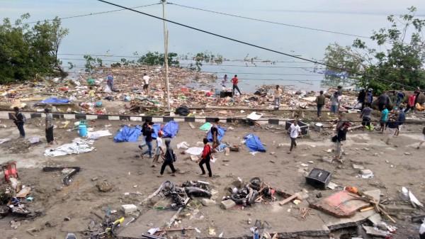 印尼蘇拉威西島遭強震、海嘯襲擊,至今傳出至少30人死亡。圖為災民走過巴路市海灘上藍布覆蓋的遺體。(法新社)