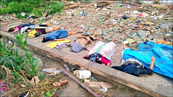 印尼中蘇拉威西省首府巴路市遭海嘯侵襲,大批民眾避難不及慘遭吞噬,街道上遍布尋獲的遺體。 (法新社)