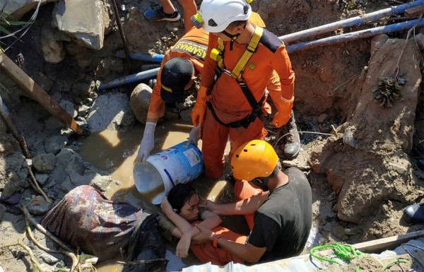 印尼救難人員在瓦礫中救出受困女子。(路透)