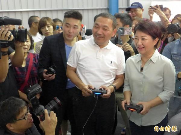 國民黨兩位市長參選人侯友宜(左)、盧秀燕(右)在侯的競選總部打電動。(記者李雅雯攝)