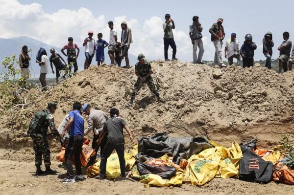 印尼當局將強震海嘯罹難者遺體,掩埋在10公尺寬、100公尺長的亂葬崗。(歐新社)