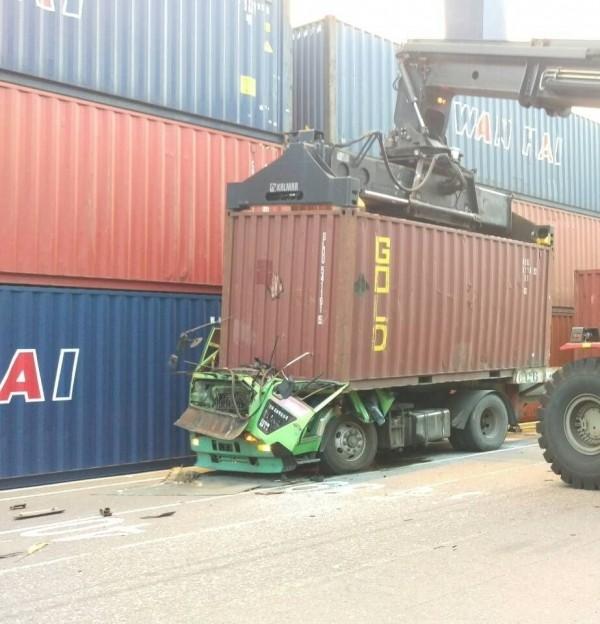掉落的貨櫃壓毀貨櫃車的車頭及車身。(記者洪定宏翻攝)