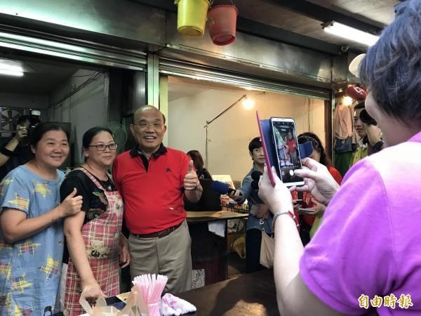民進黨新北市長參選人蘇貞昌到汐止區橫科市場拜票,攤商和其熱情合影。(記者李雅雯攝)