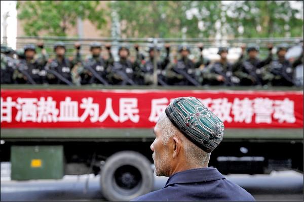 在新疆維吾爾自治區首府烏魯木齊,一名維族男子看著滿載武警的卡車駛過。(路透檔案照)