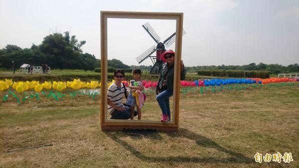 遊客以大風車為背景拍下美照。(記者楊金城攝)