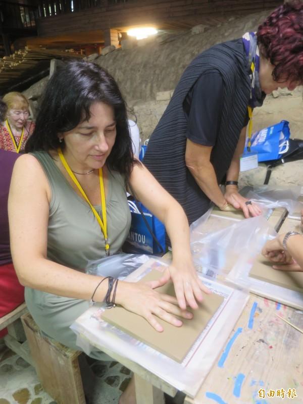 聯合國教科文組織的國際陶藝學會成員前往水里蛇窯參訪,並在陶土板上留下手印。(記者劉濱銓攝)