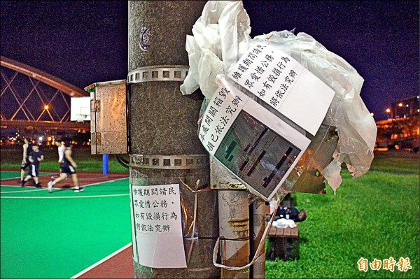 彩虹河濱公園籃球場照明燈電箱毀損、遭竊電,公園路燈管理處貼上地檢署傳票警告民眾。(記者黃捷攝)