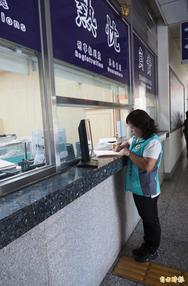 何惠娟在南投地檢署法警室填具控告公所的資料。(記者陳鳳麗攝)