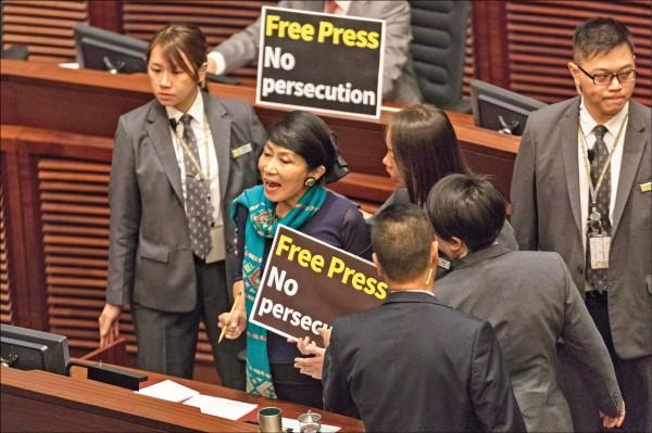 香港泛民主派議員毛孟靜十日在議場舉起「捍衛新聞自由」和「停止打壓記者」標語,試圖對發表施政報告的特首林鄭月娥表達抗議。(歐新社)