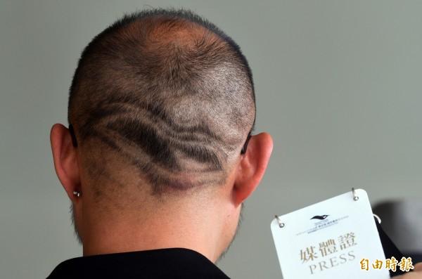 衛武營國家藝術總監簡文彬,為了「行銷」衛武營,特地將衛武營LOGO剃入髮型,希望帶給人微笑的心情。(記者張忠義攝)