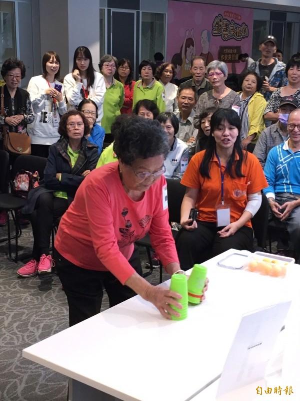 高齡92歲的阿嬤黃賴月玩起疊杯運動沉著冷靜、不慌不忙。(記者楊綿傑攝)