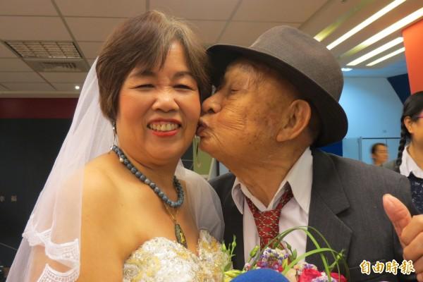 104歲人瑞新郎周懷春開心親吻披白紗的新娘倪美祝。(記者蘇孟娟攝)