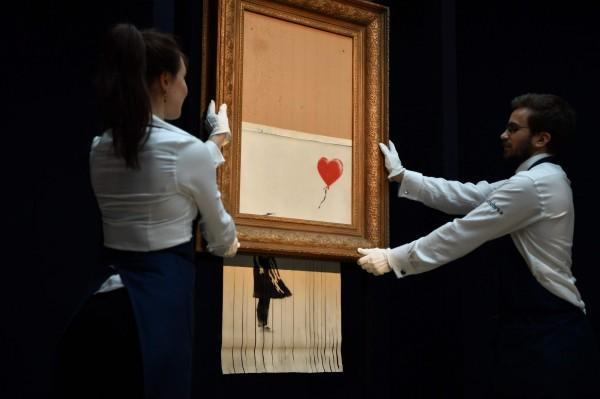 英國塗鴉藝術家班克西(Banksy)的作品《氣球女孩》自毀後,改名為《垃圾桶裡的愛》(Love is in the bin),13、14日在藝廊展出。(歐新社)