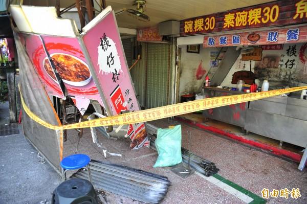 碗粿攤的燈柱被撞歪。(記者王捷攝)