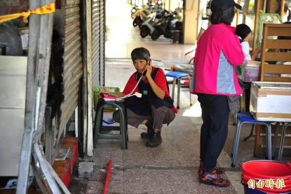 今天業者蹲在路邊做生意。(記者王捷攝)