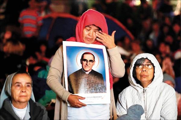 一名婦女十四日凌晨在聖薩爾瓦多,透過巨型螢幕觀看教宗方濟各冊封羅梅洛為聖人時,激動落淚。(歐新社)