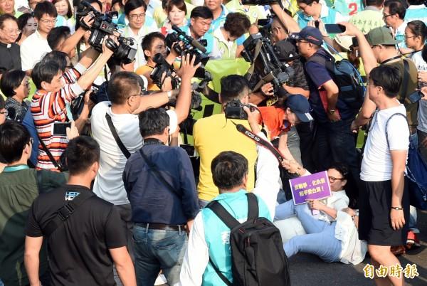 高雄市長候選人璩美鳳拿者「反戰爭、反仇恨、和平愛台灣」的牌子鬧場,遭現場工作人員架離。(記者張忠義攝)