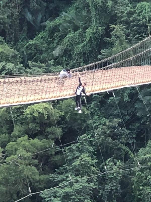 一名年輕男子為了拍照,竟只用一隻手抓住吊橋護繩,整個身體翻出吊橋外「懸掛」在橋上。(圖擷自爆料公社)