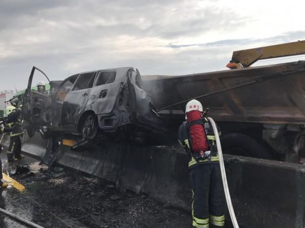 小客車被夾在砂石車及分隔島間,起火燃燒。(記者鄭名翔翻攝)
