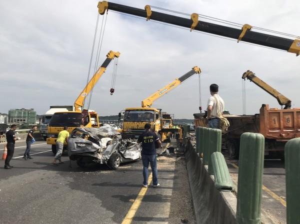 消防隊出動兩輛吊車將砂石車移開,救出受困小客車。(記者鄭名翔翻攝)