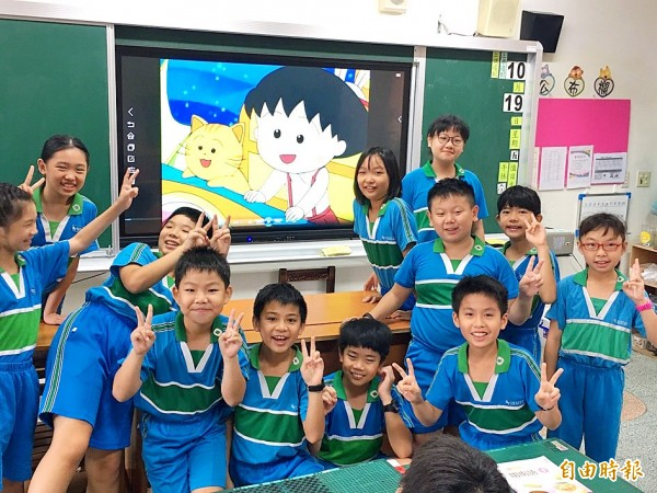Elementary-school students pose for a photograph in front of a television screen displaying a Hoklo-dubbed version of popular Japanese anime Chibi Maruko-chan in a classroom in Taipei yesterday. Photo: Lin Hsiao-yun, Taipei Times