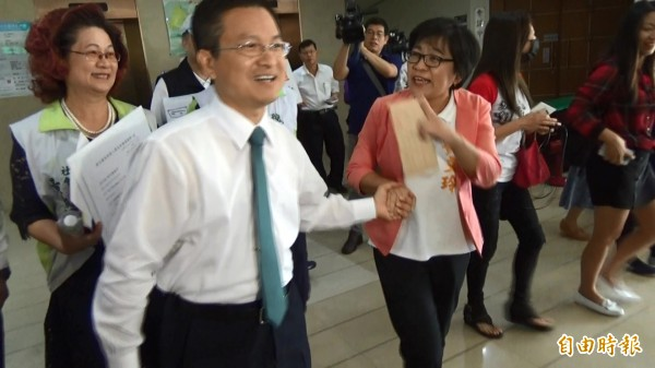 黃文玲、魏明谷於縣府電梯口手握手,上演牽手打選戰的戲碼。(記者張聰秋翻攝)