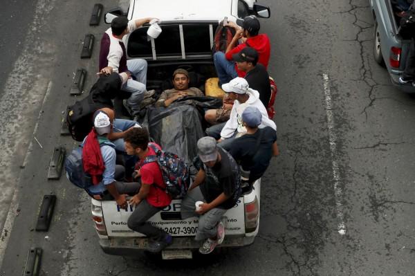 一輛輛卡車載滿移民前進美國。(歐新社)