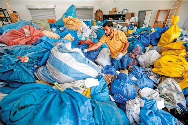 一名巴勒斯坦郵政人員忙著整理成堆的郵袋。(法新社檔案照)